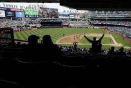 Fans cheer during the seventh inning stretch during in the first baseball game of a doubleheader between the New York Yankees and the Baltimore Orioles at Yankee Stadium Wednesday, May 15, 2019, in New York. (AP Photo/Frank Franklin II)