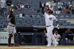 New York Yankees' Gleyber Torres, right, gestures as he runs past Baltimore Orioles catcher Austin Wynns, left, after hitting a home run during the fourth inning of a baseball game Wednesday, May 15, 2019, in New York. (AP Photo/Frank Franklin II)