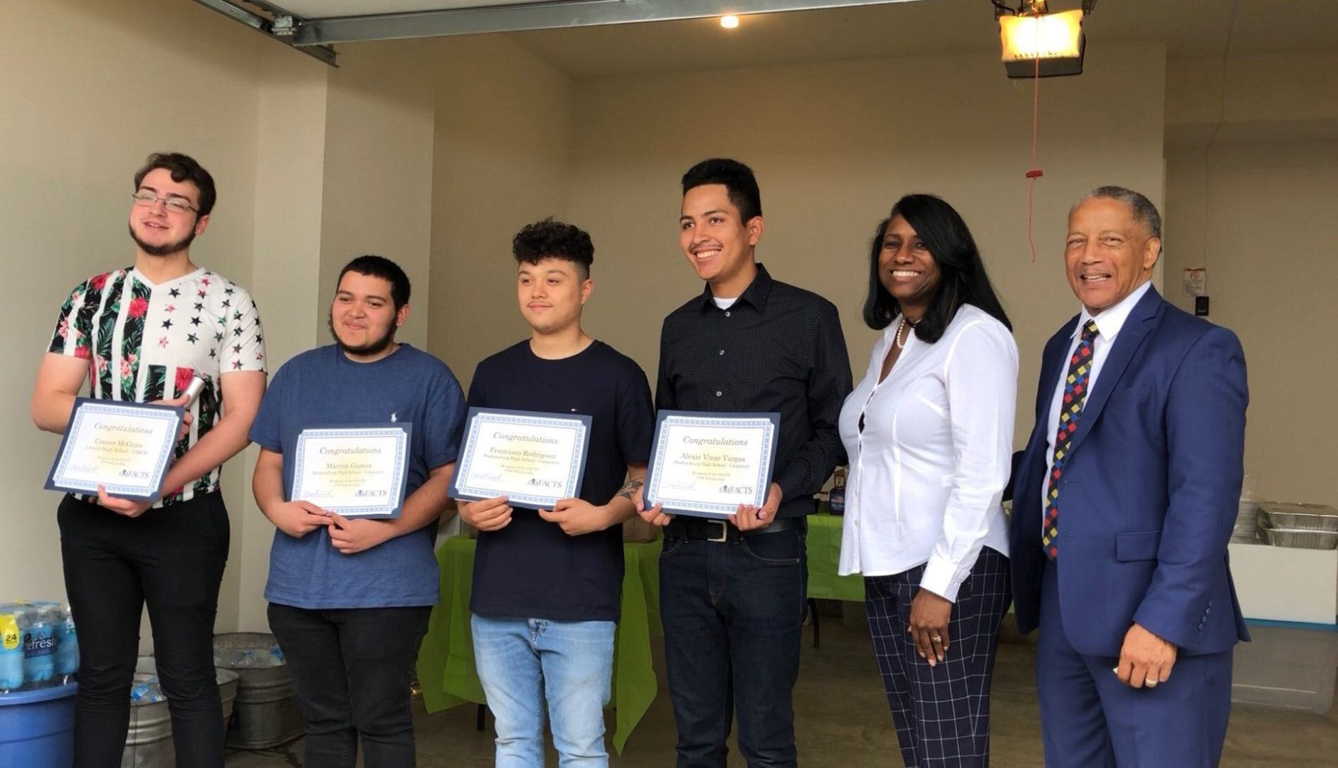 Conner McGuire, Marvin Gamez, Alexis Vivar Vargas and Francisco Rodriguez, the winners of $700 scholarships, are pictured with Prince George's County School Board member Sonya Williams and FACT Chair Howard Burnett. (WTOP/Kristi King)
