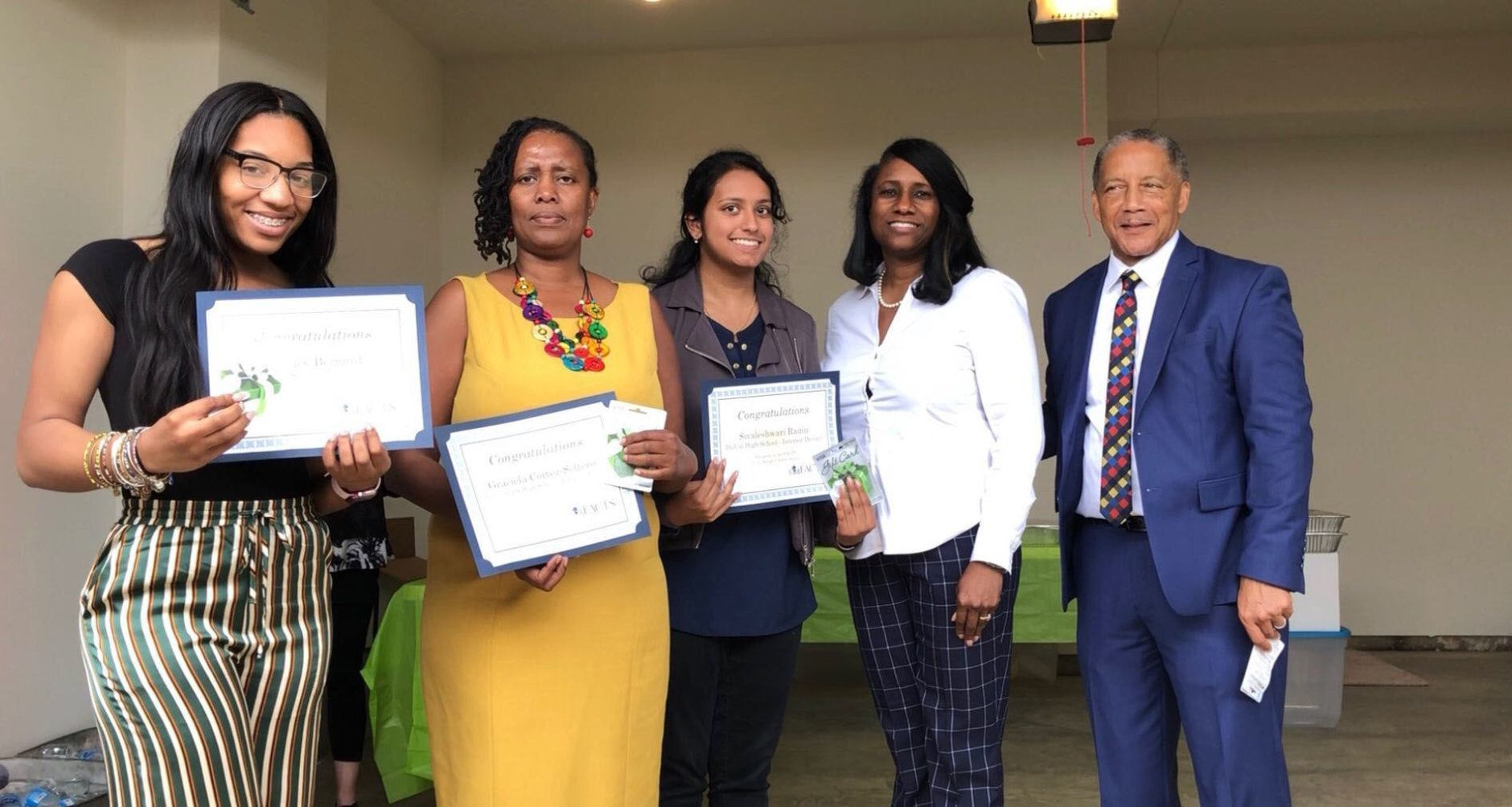 Sivaleshwsri Ramu, center, of Duval High School, was presented a $125 Design Contest Award. Also picured are dministrators who picked up awards for other students not in attendance. (WTOP/Kristi King)