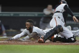 Detroit Tigers' Niko Goodrum, left, is safe at home, as Baltimore Orioles catcher Austin Wynns tries to make the tag, after a double by Nicholas Castellanos during the fourth inning of a baseball game Wednesday, May 29, 2019, in Baltimore.(AP Photo/Gail Burton)