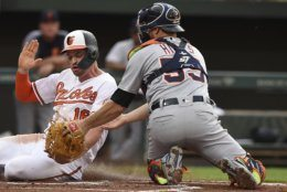 Baltimore Orioles' Trey Mancini, left, is safe at the plate, as Detroit Tigers catcher John Hicks tries to make the tag, on a double by Renato Nunez during the first inning of a baseball game Wednesday, May 29, 2019, in Baltimore. (AP Photo/Gail Burton)