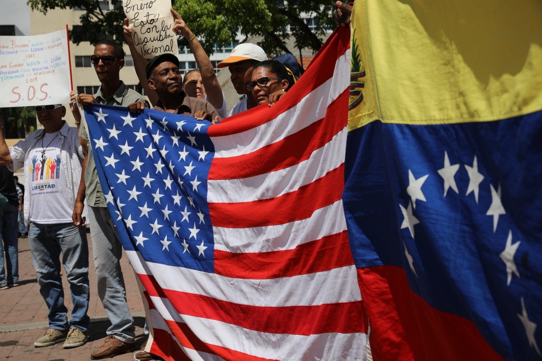Opponents of the Nicolas Maduro government hold national flags representing the U.S, and Venezuela, as they wait for the arrival of opposition leader Juan Guaidó to lead a rally in Caracas, Venezuela, Saturday, May 11, 2019. Guaidó has called for nationwide marches protesting the Maduro government, demanding new elections and the release of jailed opposition lawmakers. (AP Photo/Rodrigo Abd)