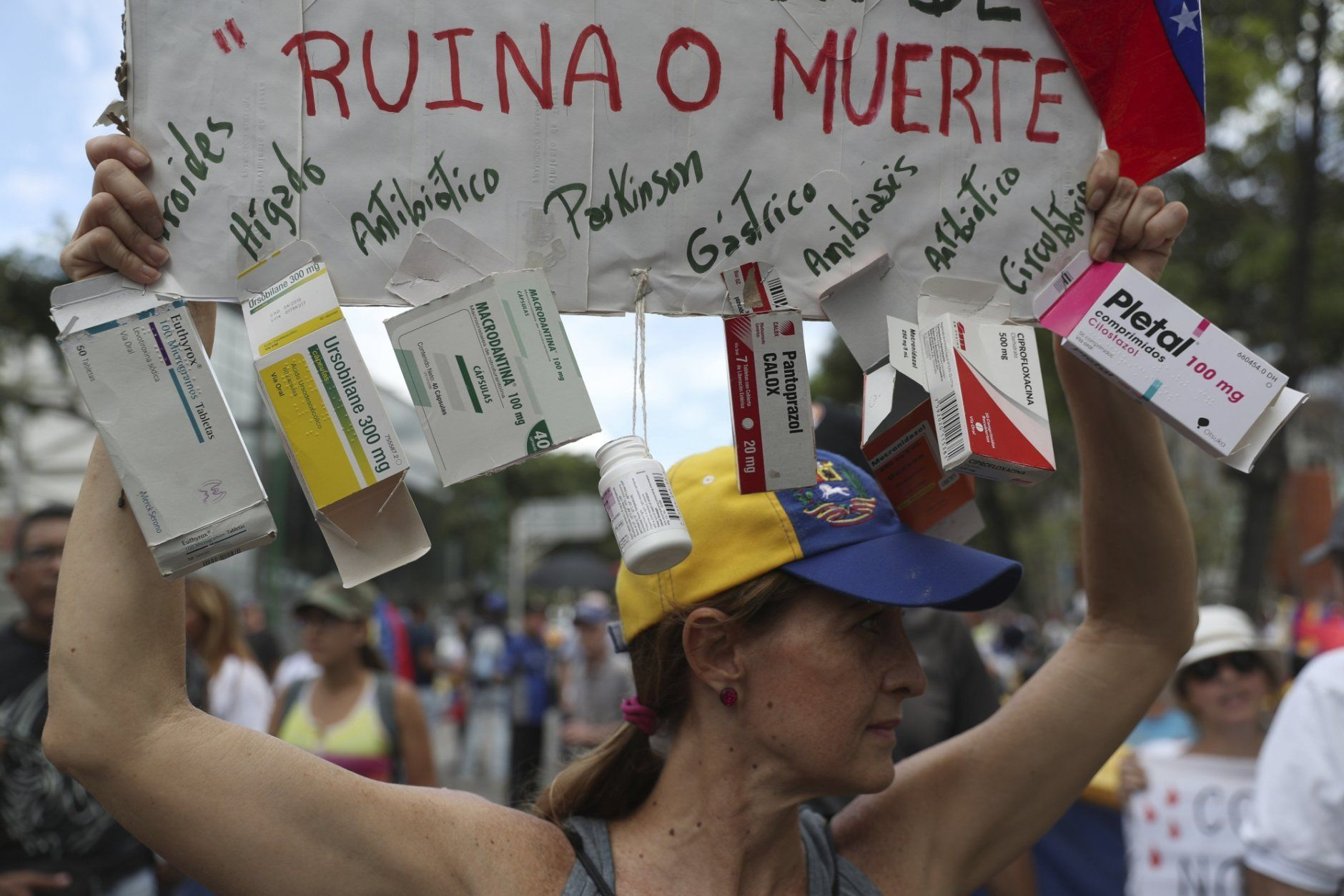 "An opponent of the Nicolas Maduro government holds up a homemade poster from which hang empty boxes of medication with a message that reads in Spanish: ""Ruin or death"" as she waits for the arrival of opposition leader Juan Guaidó to lead a rally in Caracas, Venezuela, Saturday, May 11, 2019. Guaidó has called for nationwide marches protesting the Maduro government, demanding new elections and the release of jailed opposition lawmakers. (AP Photo/Martin Mejia)"