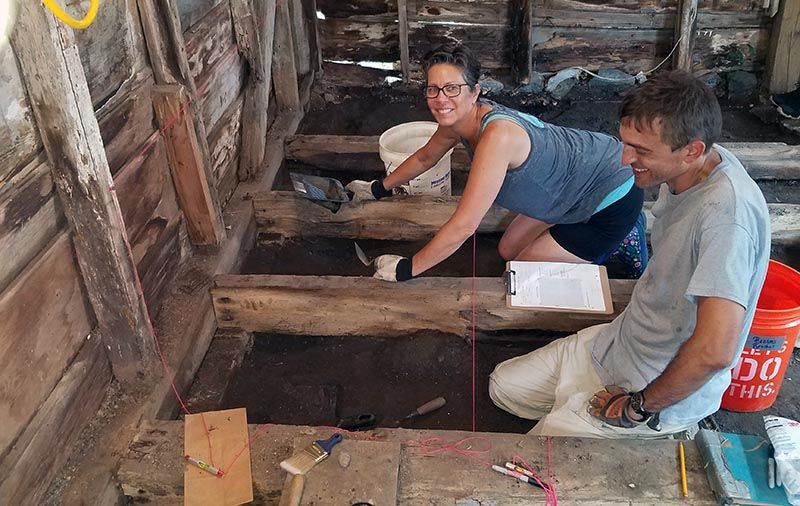 Catherine Morrison, the current owner of the Bayly propter, working with an archaeologist to excavate artifacts beneath the floorboards. (Courtesy Dorchester County)