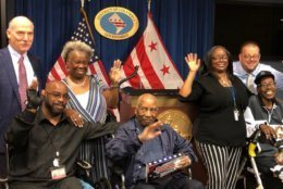 Leroy Tonic, middle, is surrounded by his family and members of the D.C. council on Friday, May 24, 2019. From left, D.C. Council Chair Phil Mendelson, Haleem Tonic, Bernadette Barnett, Leroy Tonic, Taenia Tonic, D.C. spokesman Josh Gibson and Leroy Milton Tonic Jr.(WTOP/Kristi King)
