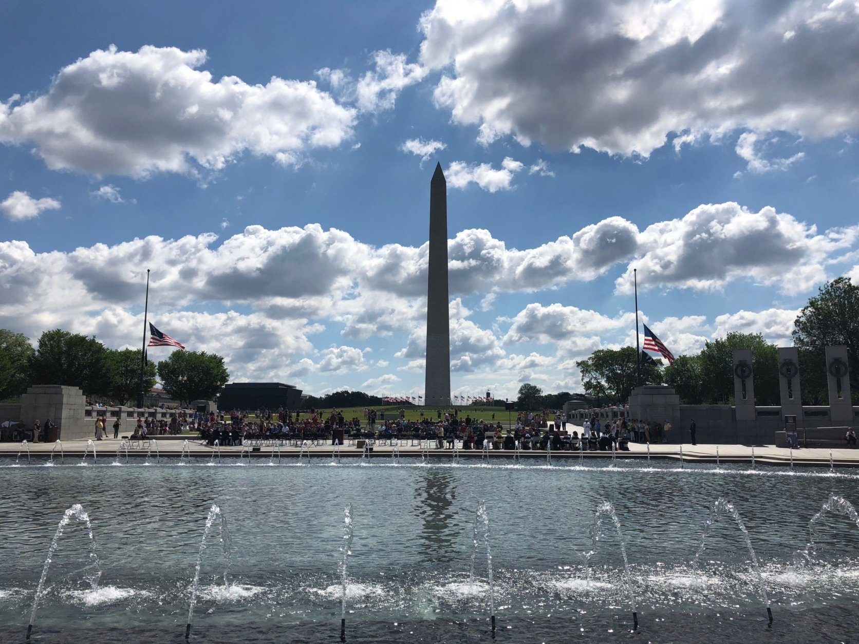 A crowd looks on at the World War II Memorial as veterans lay honorary wreaths on Monday, May 27, 2019. (WTOP/Keara Dowd)