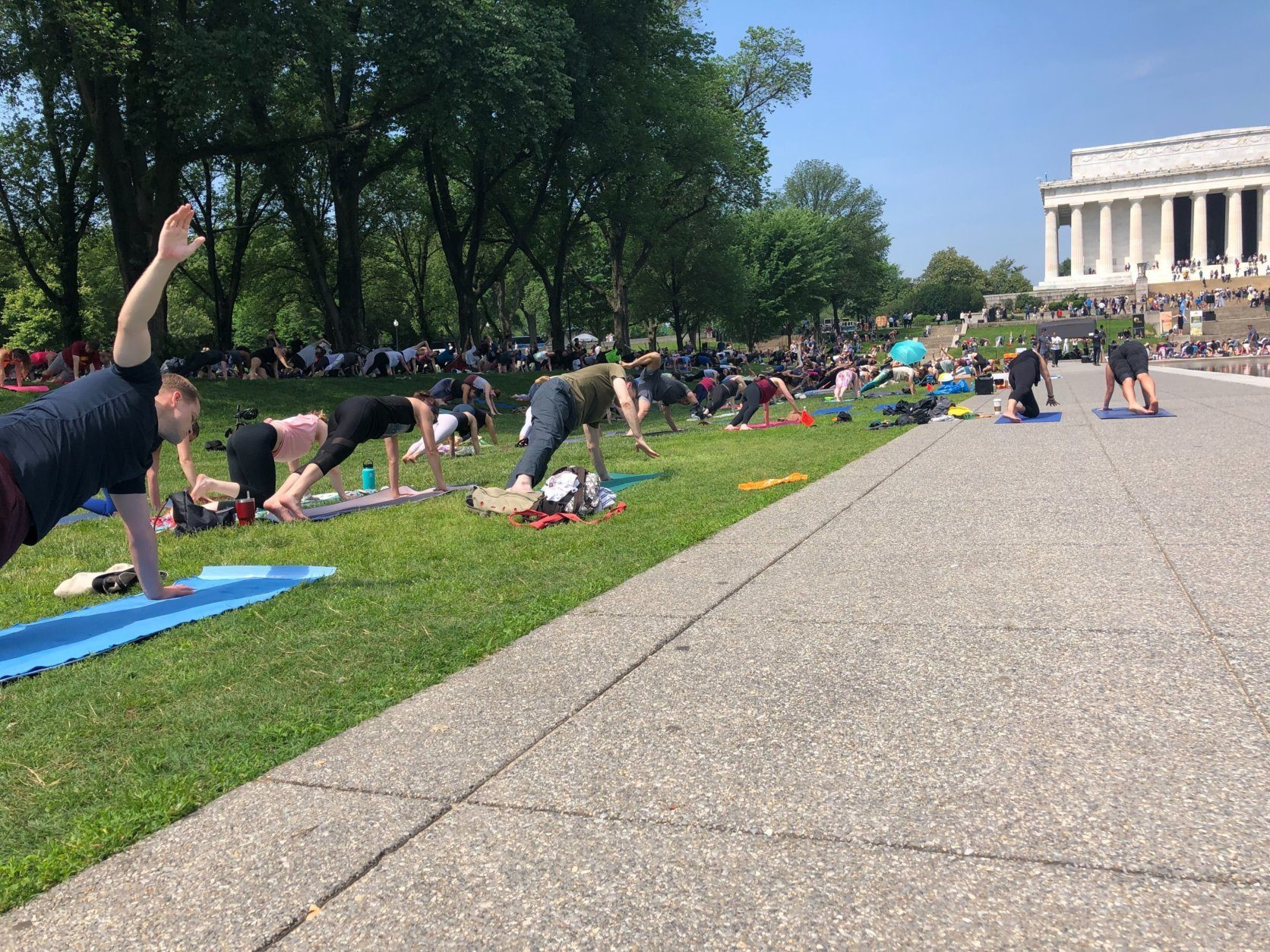 Despite sweltering temperatures, thousands brought their yoga mats to the National Mall on Sunday, May 19, 2019. (WTOP/Keara Dowd)
