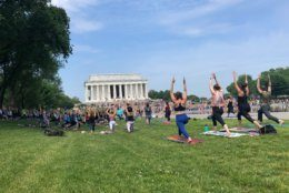 Temperatures were hovering in the upper 80s, near 90 on Sunday, but that didn't stop these yogis from holding a session on the National Mall. (WTOP/Keara Dowd)