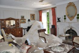 The downstairs formal living room is seen here heavily damaged from the firefighter response. On the black baseball bat near the No. 13 evidence marker, investigators found Vera Figueroa's DNA on the handle. Prosecutors believe she tried to fight back against the intruder. (Courtesy U.S. Attorney for D.C.)