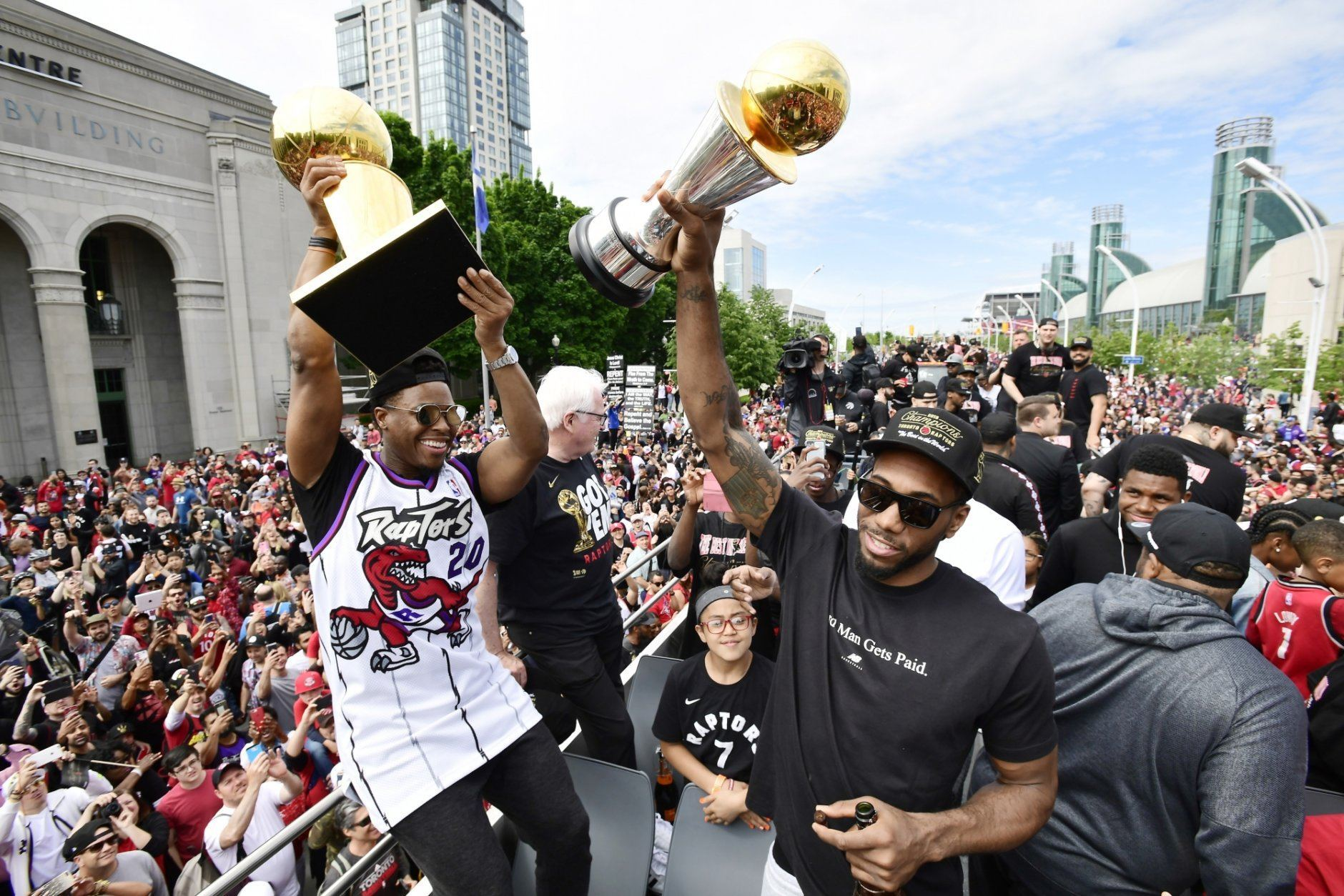Toronto Raptors guard Kyle Lowry, left, holds the Larry O'Brien Championship Trophy as forward Kawhi Leonard holds his playoffs MVP trophy  during the NBA basketball championship team's victory parade in Toronto, Monday, June 17, 2019. (Frank Gunn/The Canadian Press via AP)