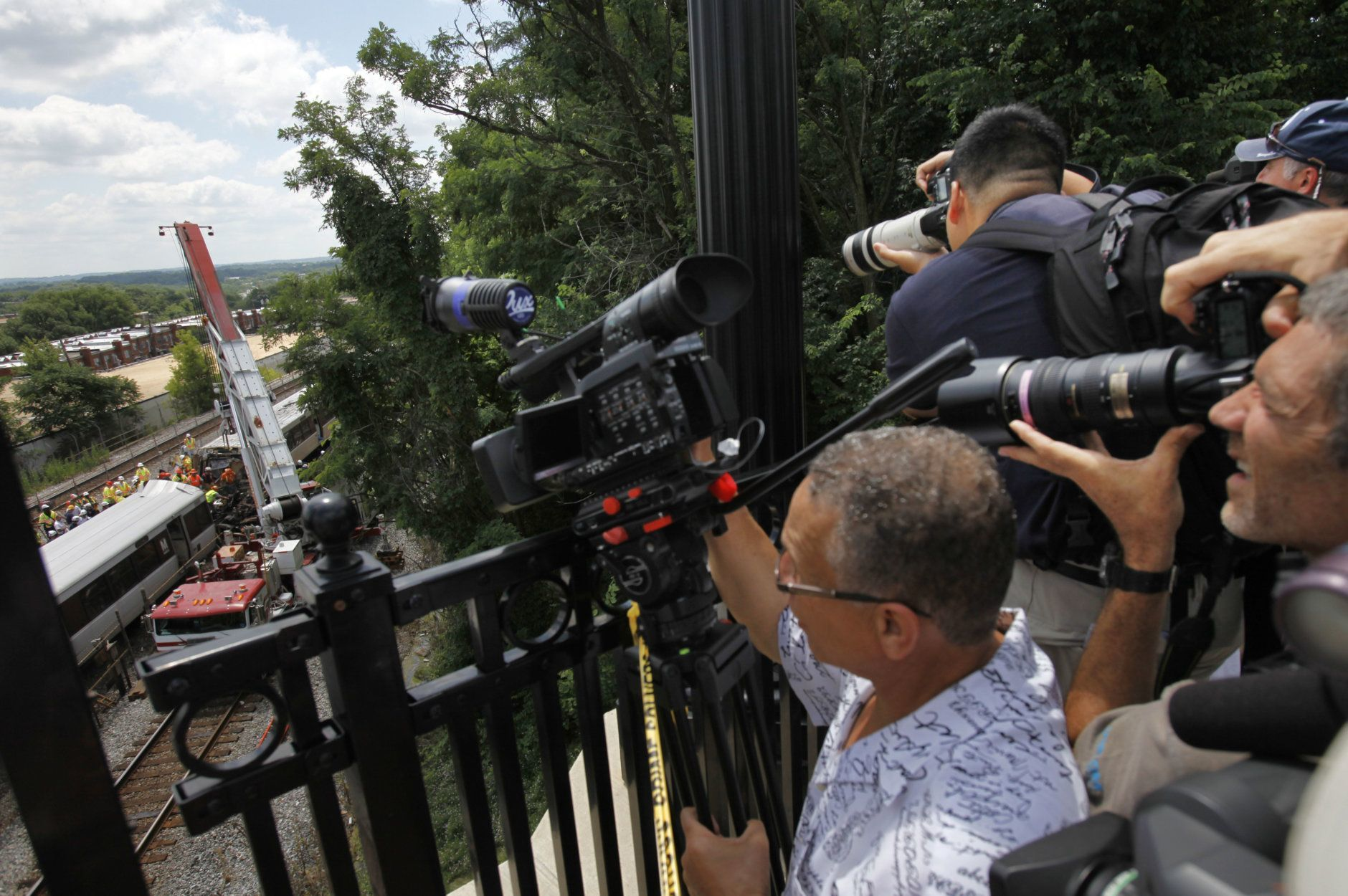 Members of the media record emergency personnel as they work at the site in Washington, Tuesday, June 23, 2009, where two metro trains collided on Monday. (AP Photo/Jacquelyn Martin)