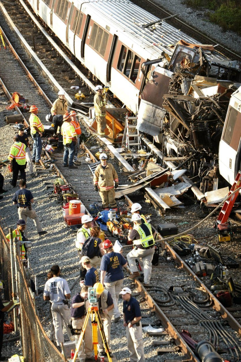 Investigators and officials look over the collision scene of two Metro transit trains in Northeast Washington, Tuesday, June 23, 2009. (AP Photo/Gerald Herbert)