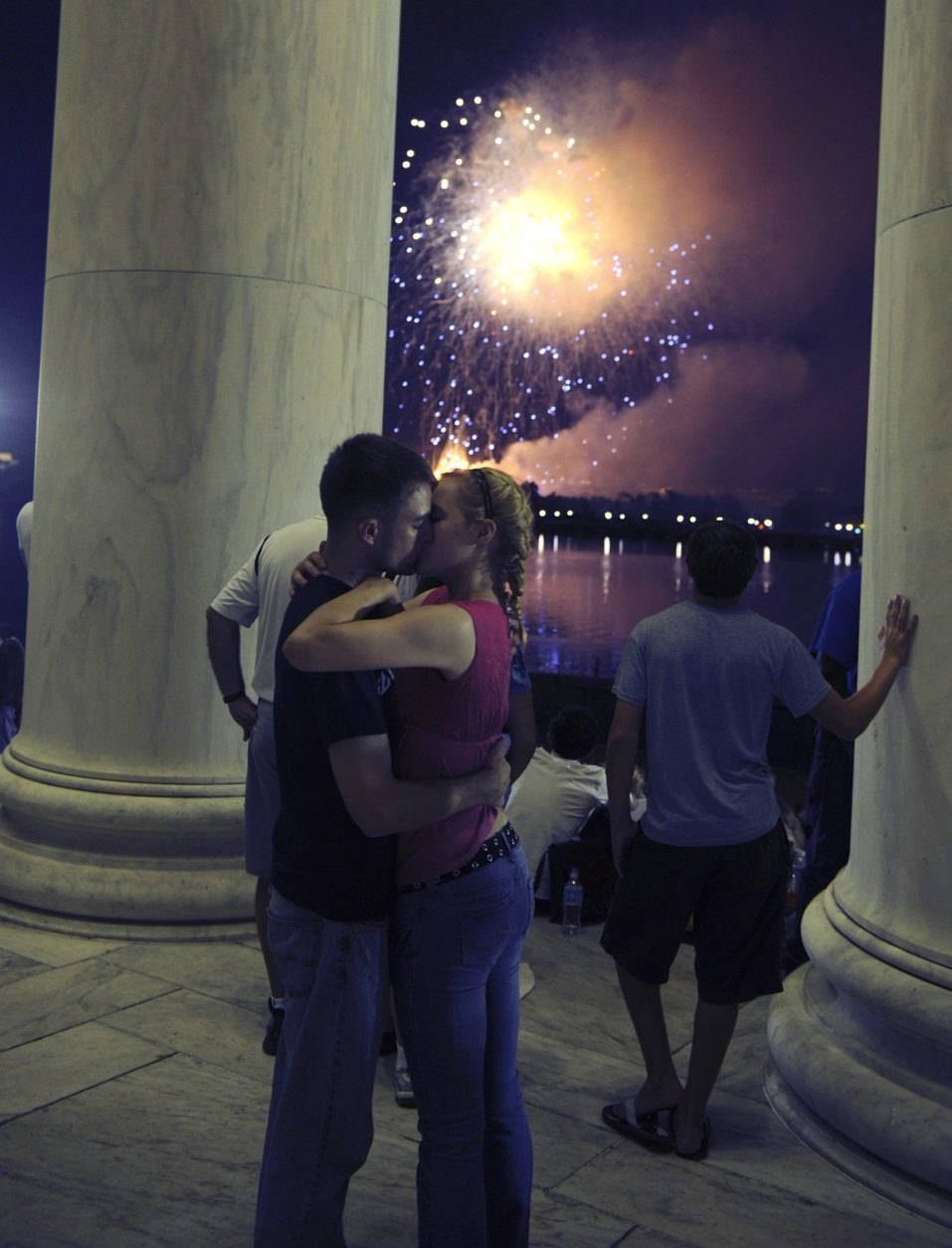 U.S. Marines Jenna Ahles, 20, of La Crosse, Wis., right, and Jack Eubanks, 25, of Kennesaw, Ga., kiss while fireworks explode over Washington while viewing from the Jefferson Memorial, Monday, July 4, 2011. (AP Photo/Cliff Owen)