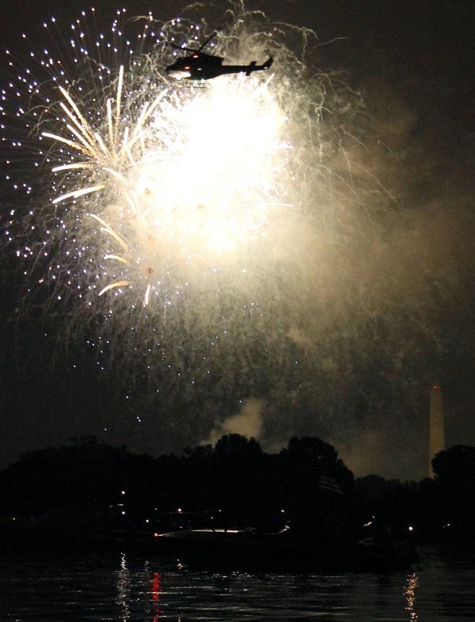 A helicopter flies by as fireworks illuminate the night sky and are reflected in the Potomac River with the Washington Monument at right on Monday, July 4, 2011 in Washington. (AP Photo/Alex Brandon)