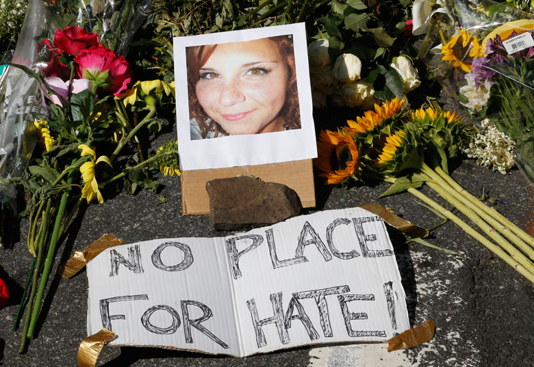 FILE- In this Aug. 13, 2017 file photo, a photo of Heather Heyer rests among a makeshift memorial in Charlottesville, Va. Heyer was struck and killed by a car while protesting a white nationalist rally on Aug. 12. The city of Charlottesville is preparing to dedicate a downtown street in her honor. (AP Photo/Steve Helber, File)