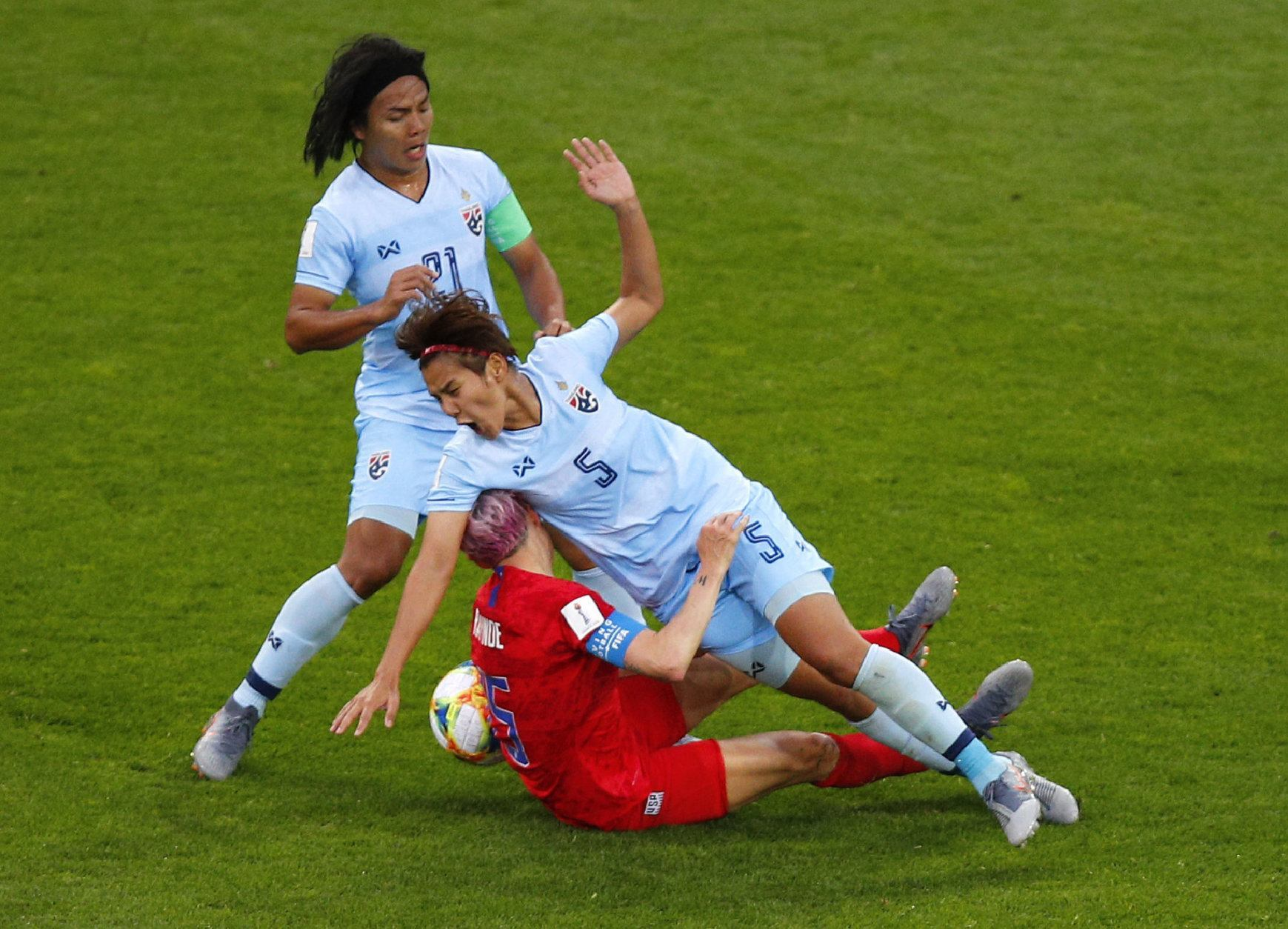 United States' Megan Rapinoe, centre, collides with Thailand's Ainon Phancha, right, as Kanjana Sung-Ngoen, left, watches during the Women's World Cup Group F soccer match between the United States and Thailand at the Stade Auguste-Delaune in Reims, France, Tuesday, June 11, 2019. (AP Photo/Francois Mori)
