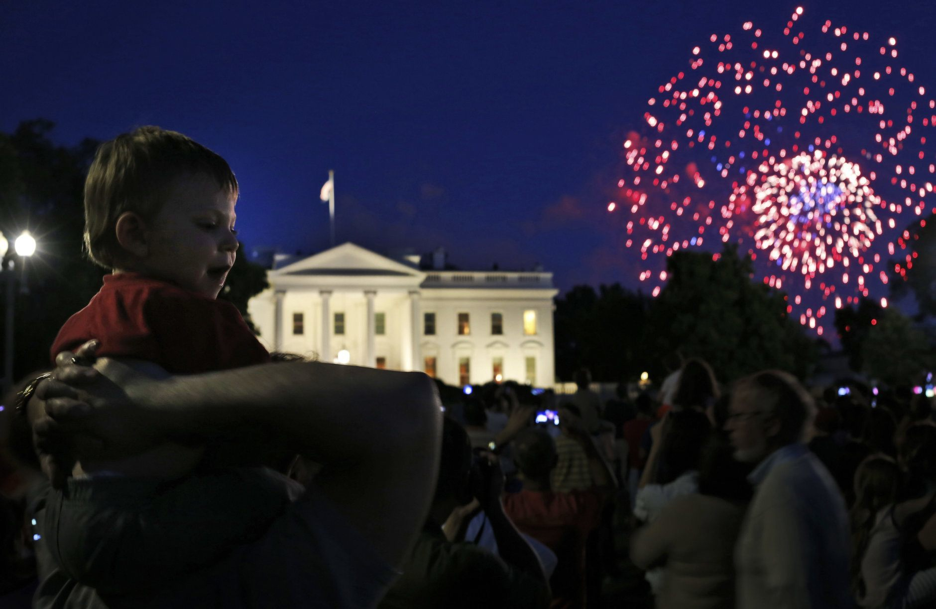 Louis Celli of Montgomery Village, Md., carries his 18-month-old grandson Jayden on his shoulders to watch the fireworks in front of the White House marking Independence Day celebrations in Washington, Friday, July 4, 2014. (AP Photo/Charles Dharapak)
