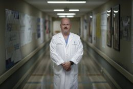 In this Wednesday, May 29, 2019 photo, Dr. Dave MacIntyre poses for a portrait at Sunrise Hospital in Las Vegas. He is part of a vast community of people touched by America's mass shootings. Traumatized after treating dozens of victims​ from a 2017 Las Vegas concert massacre, MacIntyre plans to leave surgery and help train others in coping with similar challenges. (AP Photo/John Locher)