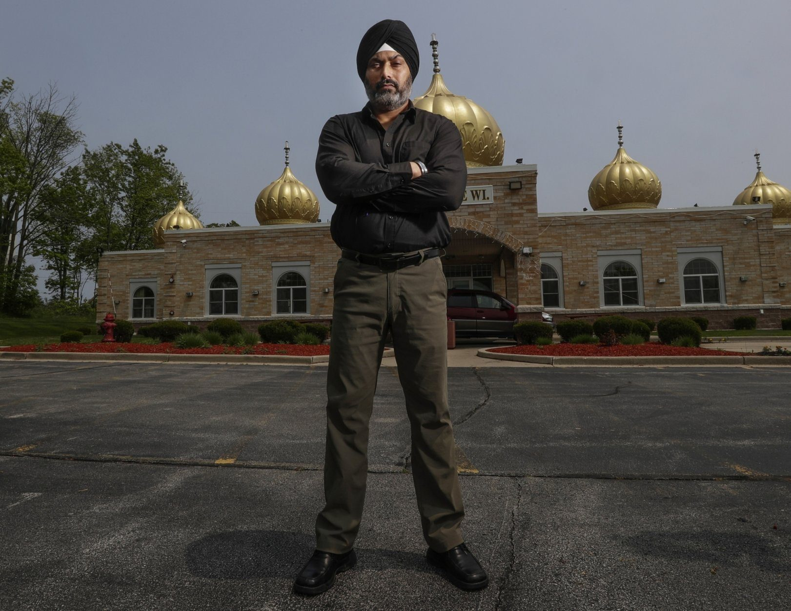 "In this Saturday, June 1, 2019 photo, Pardeep Singh Kaleka poses for a portrait outside the Sikh Temple in Oak Creek, Wis. Kaleka, whose father was one of six people killed in a 2012 mass shooting at a Sikh temple in Wisconsin, has bonded with those who've lost families in other attacks. He's traveled to Pittsburgh, Newtown, Conn. and Charleston, S.C., and says there's another instant connection with survivors from those communities. ""We're like family,"" he says. (AP Photo/Morry Gash)"