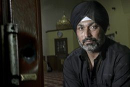 In this Saturday, June 1, 2019 photo, Pardeep Singh Kaleka poses for a portrait in the Sikh Temple in Oak Creek, Wis. At left is a bullet hole in a door frame of the church, left as a reminder of the 2012 shooting. (AP Photo/Morry Gash)