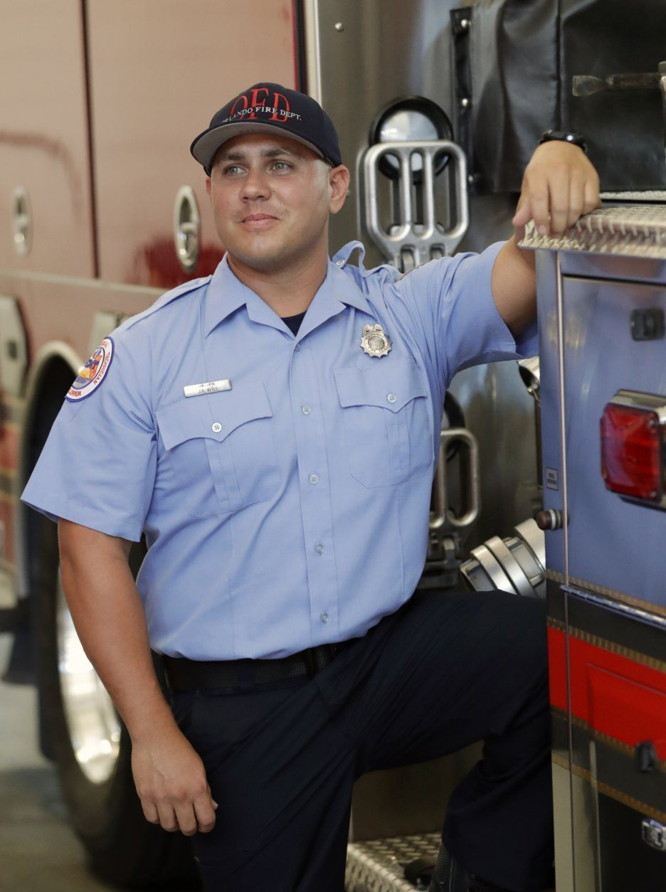 "In this Friday, May 24, 2019 photo, Orlando firefighter Jimmy Reyes poses for a portrait at his duty station in Orlando, Fla. He enrolled in a program, UCF RESTORES, a clinic at the University of Central Florida that helps first responders, members of the military and some others who've been diagnosed with PTSD. Reyes says he was haunted by the memory of tending to people who'd been shot in 2016 at the Pulse nightclub. The mass shooting left 49 dead. Reyes says the program helped, but he still deals with anxiety. ""I'm a completely different person,"" he says. (AP Photo/John Raoux)"