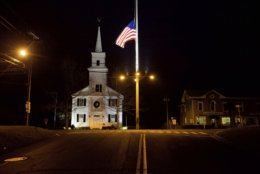 FILE - In this Saturday, Dec. 15, 2012 file photo, a U.S. flag flies at half-staff on Main Street in honor of the 26 students and staff killed in a mass shooting at the Sandy Hook Elementary school in Newtown, Conn. Most of those killed in the attack were 6-and 7-year-old students. The shooter took his own life. (AP Photo/David Goldman)