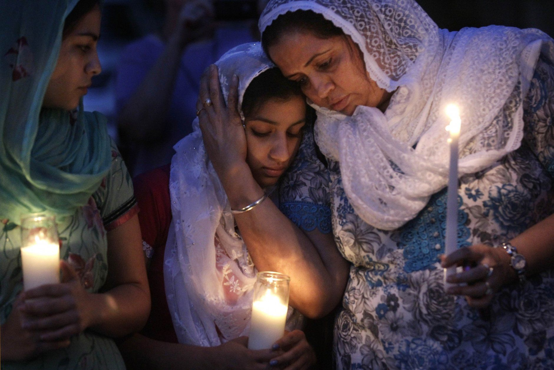 FILE - In this Monday, Aug. 6, 2012 file photo, Sikh worshipers gather for a candlelight vigil after prayer services at the Sikh Religious Society of Wisconsin in Brookfield, Wis. A gunman identified as a former leader of a white supremacist heavy metal band killed six people at the Sikh Temple of Wisconsin in Oak Creek before being shot to death by police. (AP Photo/M. Spencer Green)