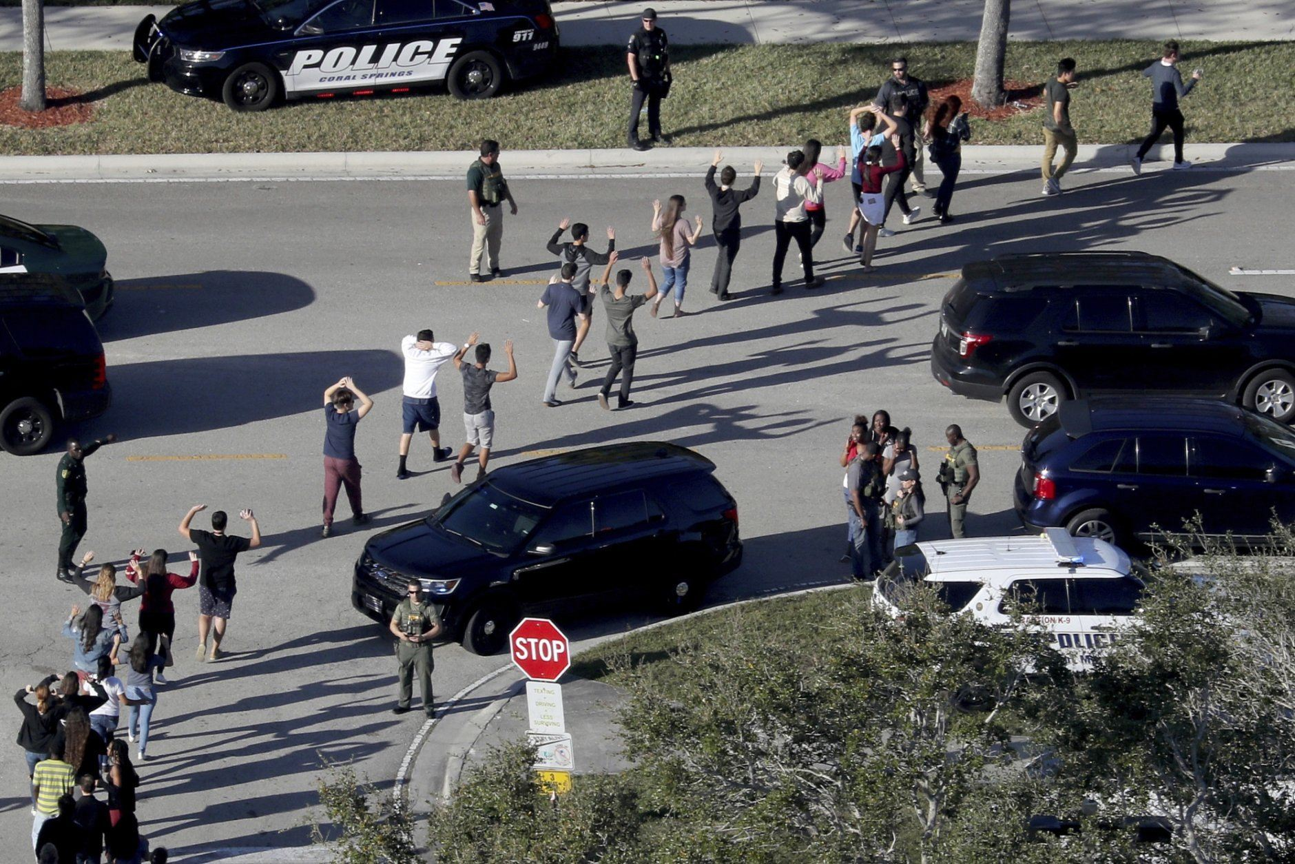 FILE - In this Wednesday, Feb. 14, 2018 file photo, students hold their hands in the air as they are evacuated by police from Marjory Stoneman Douglas High School in Parkland, Fla., after a shooter opened fire on the campus. Seventeen students and staff were killed in the attack. Parkland is one of the communities where, in the wake of mass shootings, wellness centers have opened, offering residents a place to gather and heal. (Mike Stocker/South Florida Sun-Sentinel via AP)