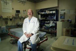 In this Wednesday, May 29, 2019 photo, Dr. Dave MacIntyre poses for a portrait in the emergency room of the Sunrise Hospital in Las Vegas. He has struggled with PTSD after treating dozens of victims there from a 2017 concert massacre. MacIntyre plans to leave surgery and help train others in coping with similar challenges. He joins a growing community of survivors touched by America's mass shootings. (AP Photo/John Locher)