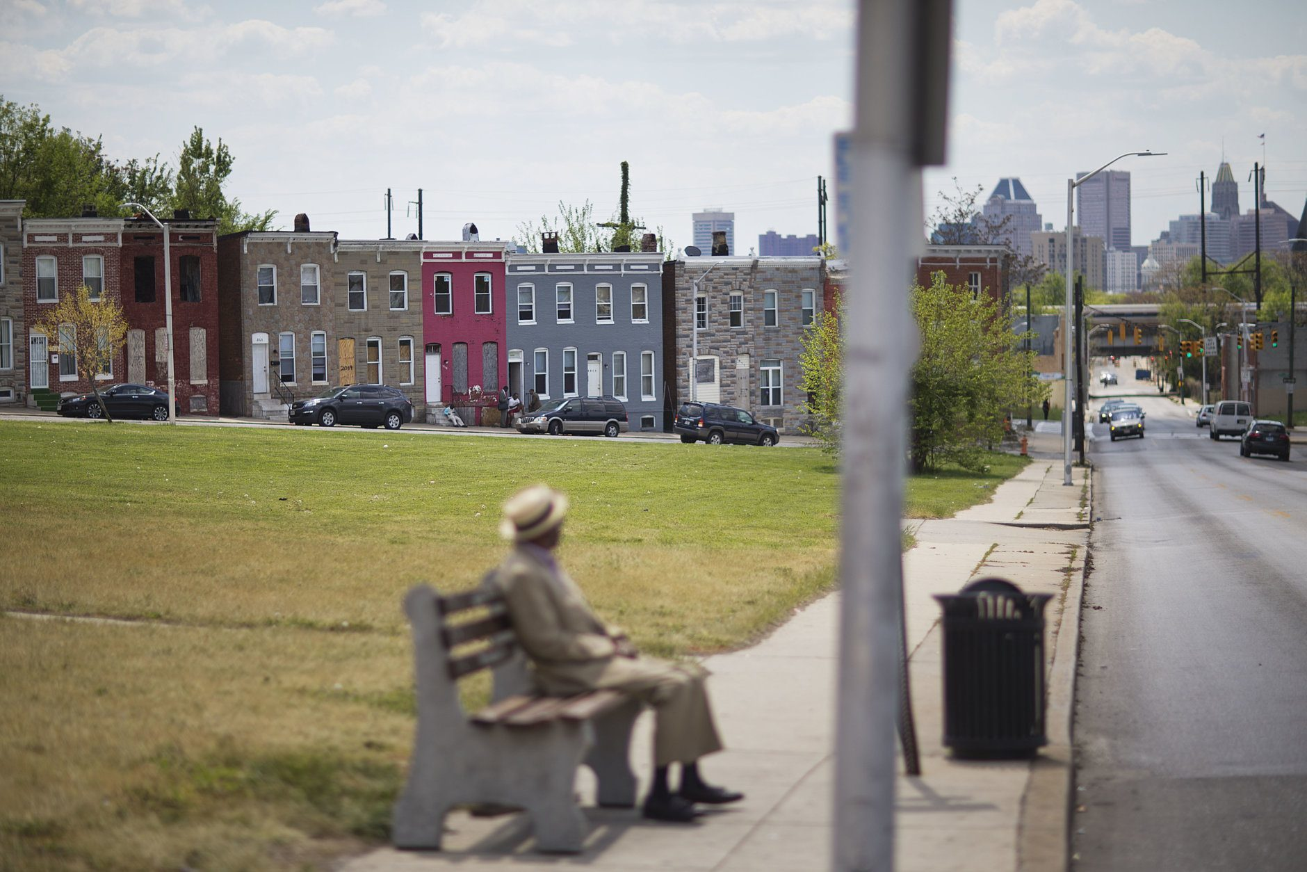 """Row houses sit behind a man waiting at a bus stop, Sunday, May 3, 2015, in Baltimore. Gov. Larry Hogan has called for a statewide """"Day Of Prayer And Peace"""" on Sunday after civil unrest rocked Baltimore. (AP Photo/David Goldman)"""