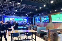 There is a sports bar on the second level. Patrons can either eat and drink inside, or have food delivered to their bays. (WTOP/Noah Frank)