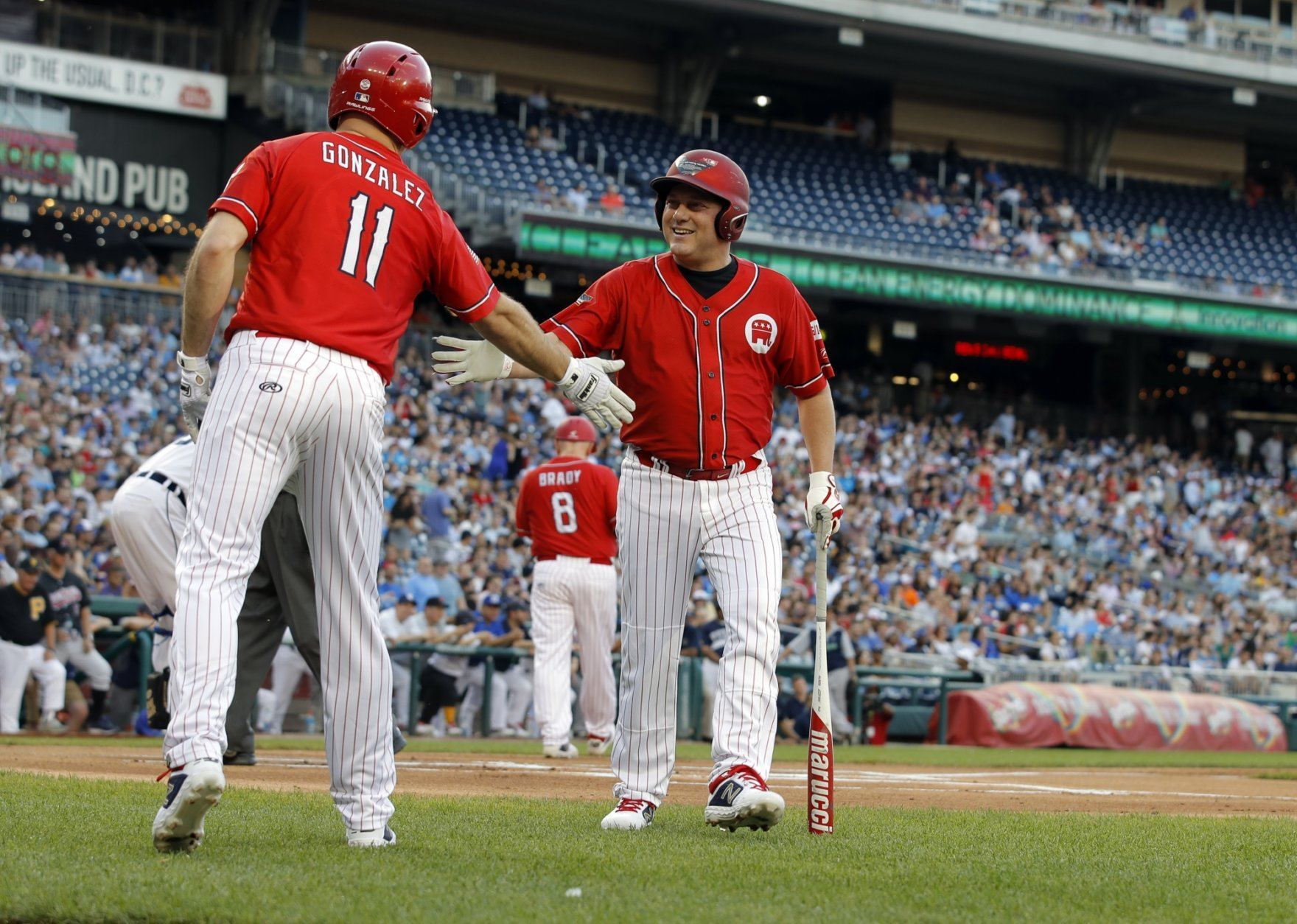 Rep. Anthony Gonzalez, R-Ohio, congratulates Rep. Steve Scalise, R-La., after he got a hit during Congressional Baseball Game at Nationals Park in Washington, Wednesday, June 26, 2019. A pinch-runner ran for Scalise. (AP Photo/Carolyn Kaster)