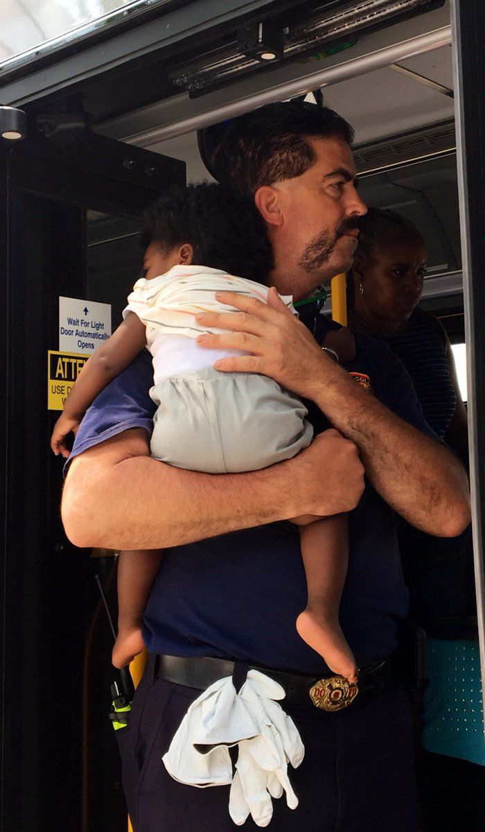 An emergency responder from D.C. Fire and EMS holds a toddler after a Metrobus and truck collided on June 1, 2019. (Courtesy D.C. Fire and EMS)