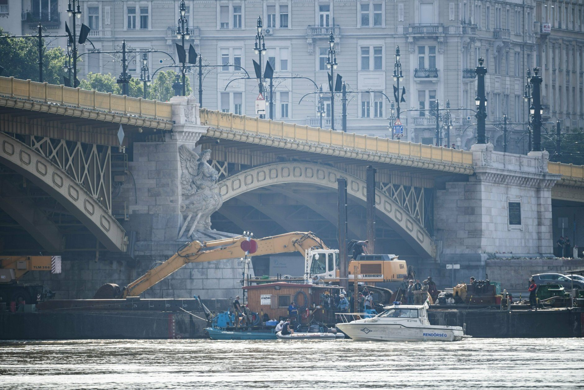 A power shovel fixed on a pontoon and members of the rescue team works in River Danube near Margaret Bridge, the scene of a boat accident, in Budapest, Hungary, Friday, June 7, 2019. A sightseeing boat carrying 33 South Korean tourists was crashed by a large river cruise ship and sank in River Danube at a pier of Margaret Bridge on May 29, killing at least nineteen tourists. Seven tourists were injured, 9 persons went missing. (Marton Monus/MTI via AP)