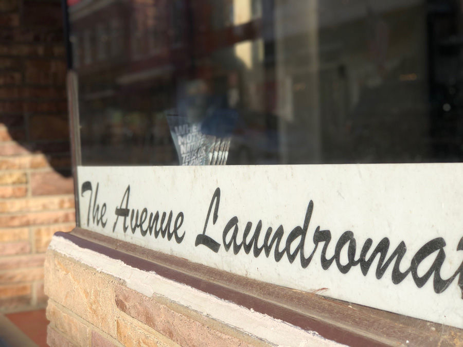 "Another sign that this is a tight-knit community is a literal sign in the business's window: Reading ""The Avenue Laudromat,"" it was made for Small by a customer. (WTOP/Kate Ryan)"