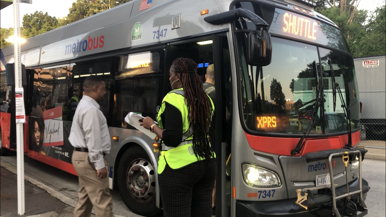 A Metro employee helps direct people using the Huntington-Pentagon shuttle June 3, 2019. (WTOP/Melissa Howell)
