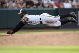 Baltimore Orioles' Jonathan Villar dives towards third on a single by Trey Mancini during the third inning of the team's baseball game against the Cleveland Indians, Saturday, June 29, 2019, in Baltimore. (AP Photo/Nick Wass)