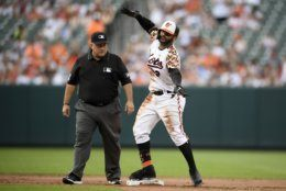 Baltimore Orioles' Jonathan Villar reacts after hitting a two-run double during the fourth inning of the team's baseball game against the Cleveland Indians, Saturday, June 29, 2019, in Baltimore. At left is second base umpire Eric Cooper. (AP Photo/Nick Wass)
