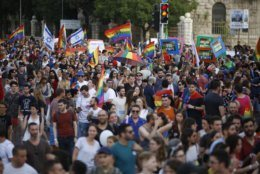 Participants wave flags and hold signs during the annual Gay Pride parade in Jerusalem, Thursday, June 6, 2019. Thousands of people are marching through the streets of Jerusalem in the city's annual gay pride parade, a festival that exposes deep divisions between Israel's secular and Jewish ultra-Orthodox camps. (AP Photo/Ariel Schalit)