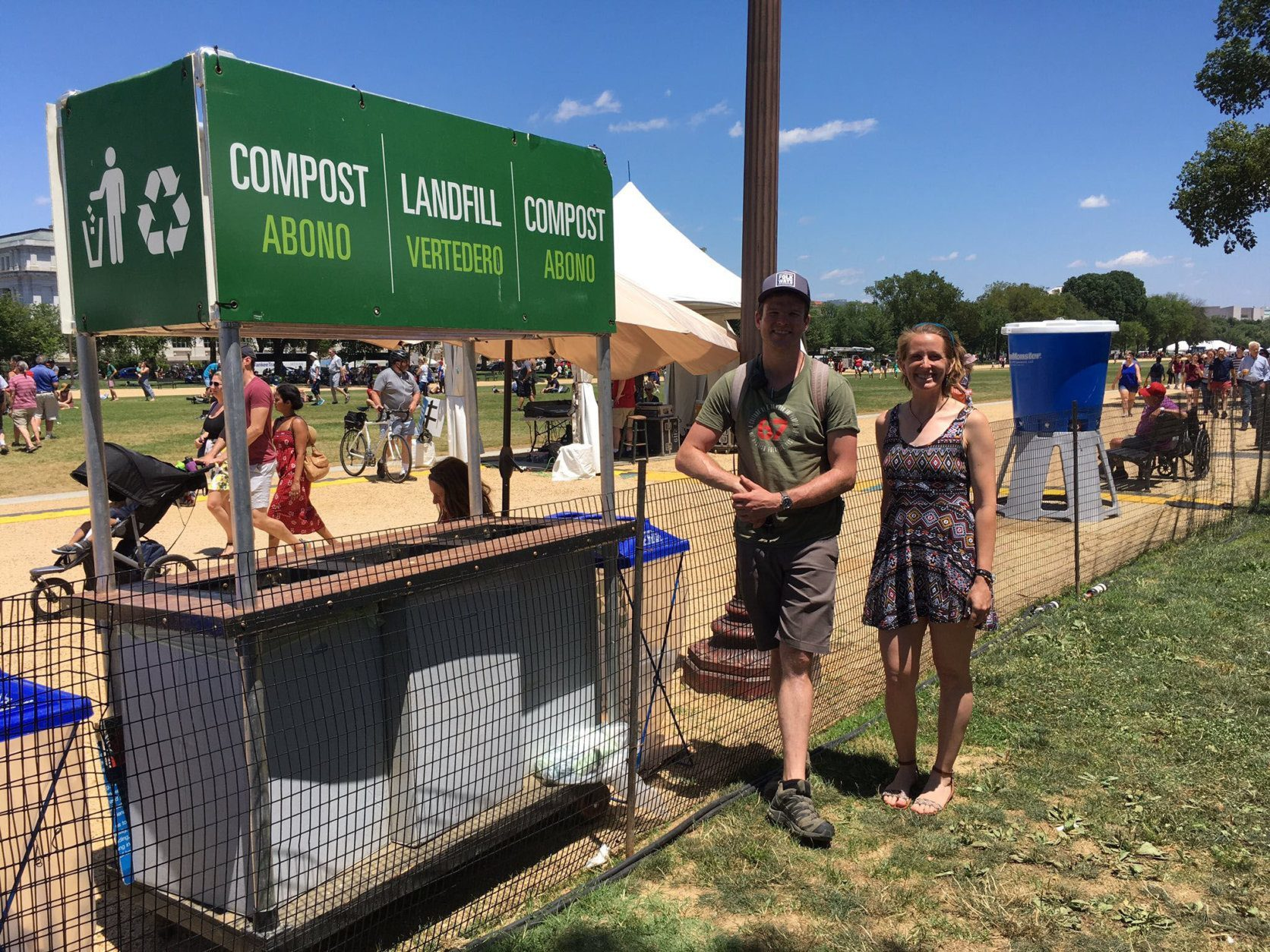 Festival operations director Justin Hensley with Kristi Blummer of the Compost Crew discuss sustainable practices at the Smithsonian Folklife Festival. (WTOP/Liz Anderson)