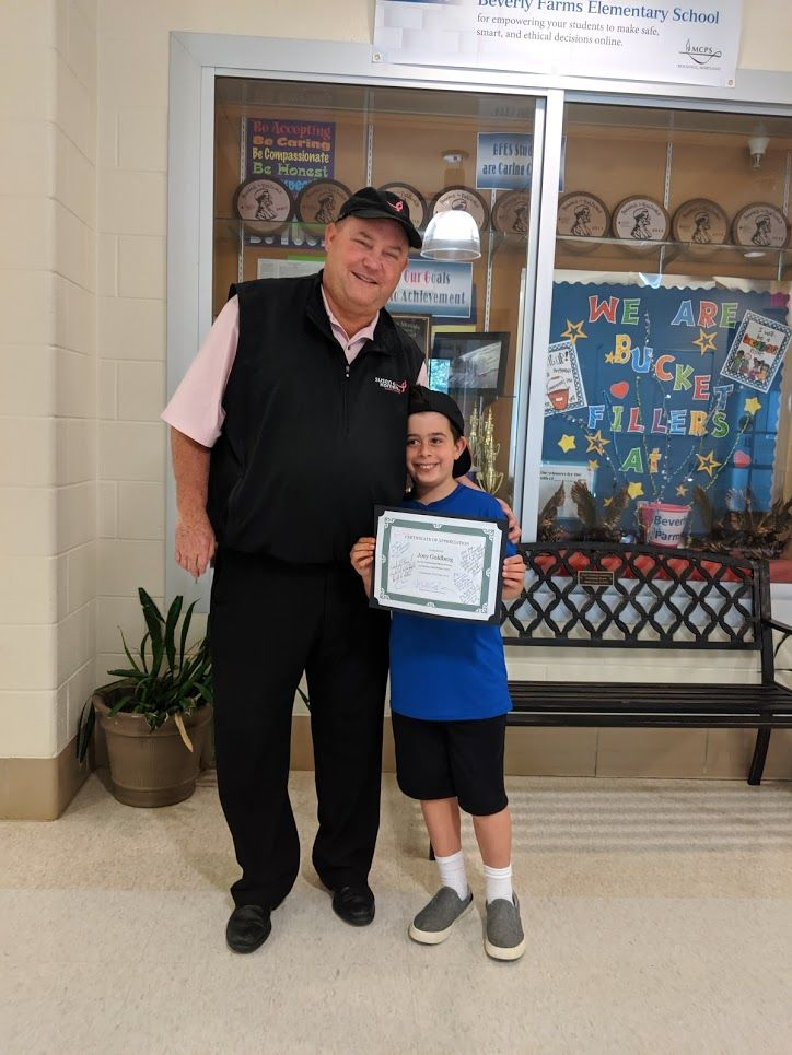 Susan G. Komen's Michael Jessup surprises 8-year-old Joey Goldberg at his school. Goldberg raised $1,300 for the organization in honor of his mother.  (Courtesy Aaron Goldberg)