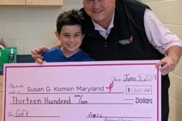 Susan G. Komen's Michael Jessup surprises Joey Goldberg with a check he could sign and give back to the foundation. Goldberg raised $1,300 to fight cancer. (Courtesy Aaron Goldberg)