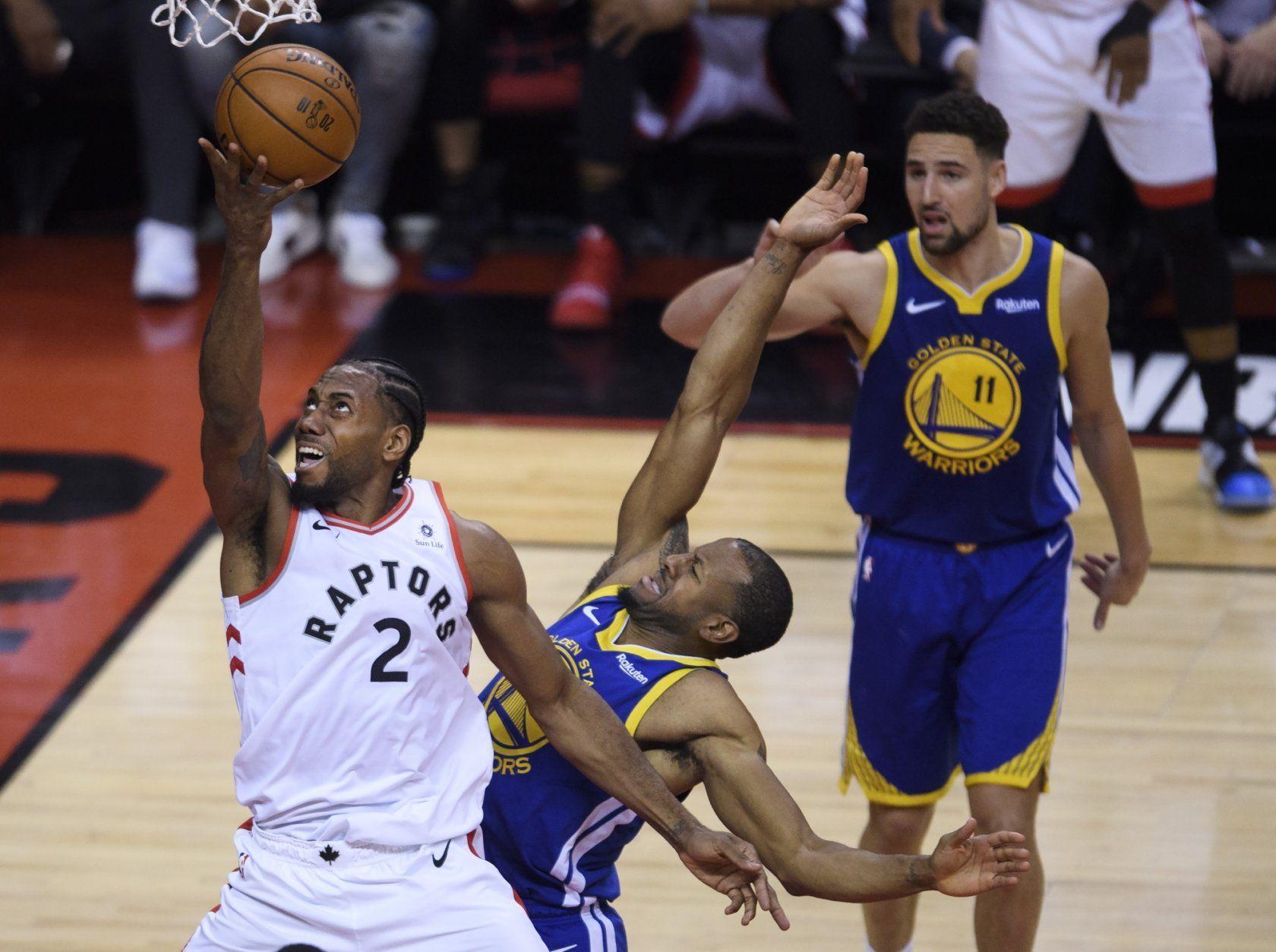 Toronto Raptors forward Kawhi Leonard (2) drives past Golden State Warriors forward Andre Iguodala during first-half basketball action in Game 5 of the NBA Finals in Toronto, Monday, June 10, 2019. (Nathan Denette/The Canadian Press via AP)