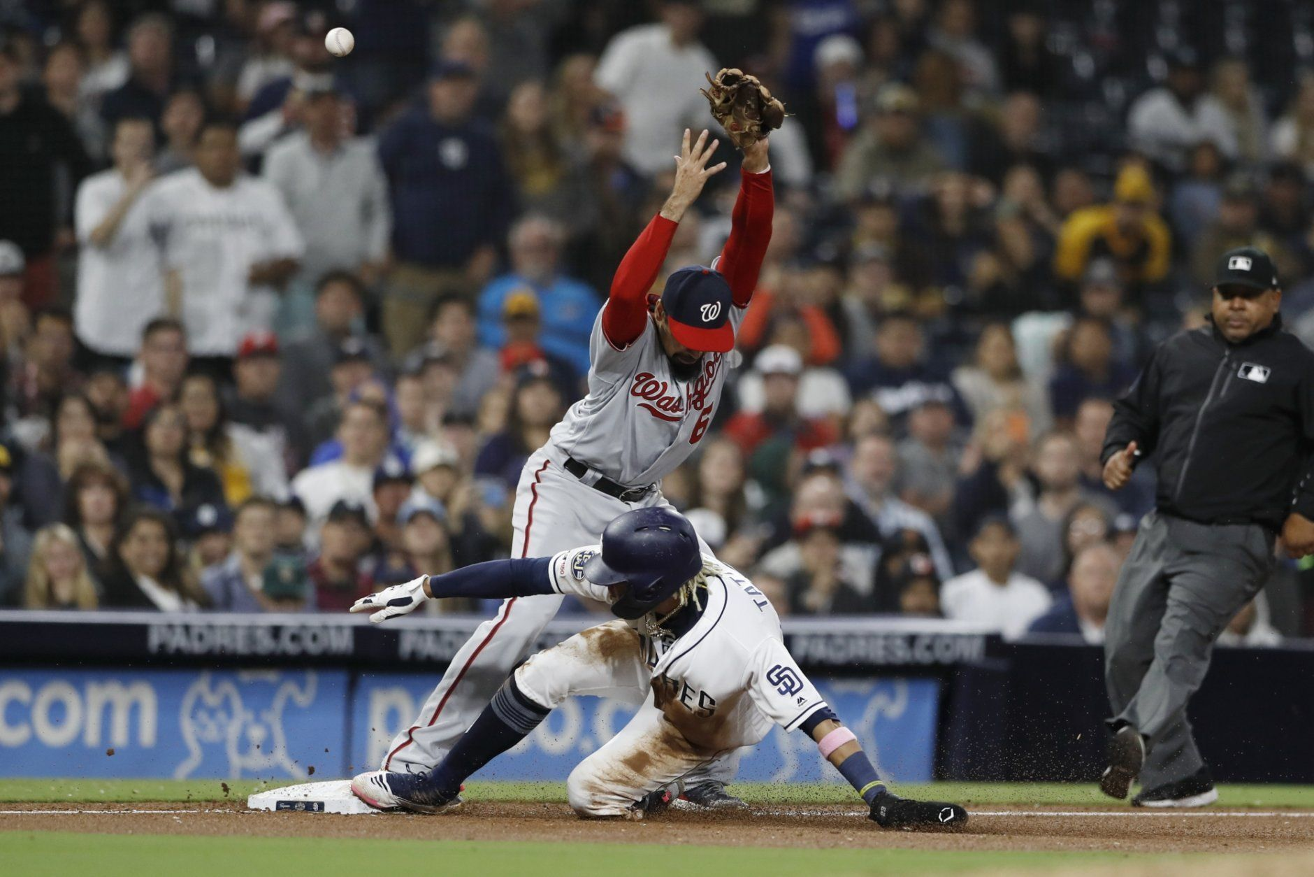 San Diego Padres' Fernando Tatis Jr., below, slides in safely to third on a grounder by Manny Machado, as Washington Nationals third baseman Anthony Rendon can't make the catch during the eighth inning of a baseball game Thursday, June 6, 2019, in San Diego. Tatis scored on the play, advancing on the error by Rendon. Manuel Margot also scored. (AP Photo/Gregory Bull)