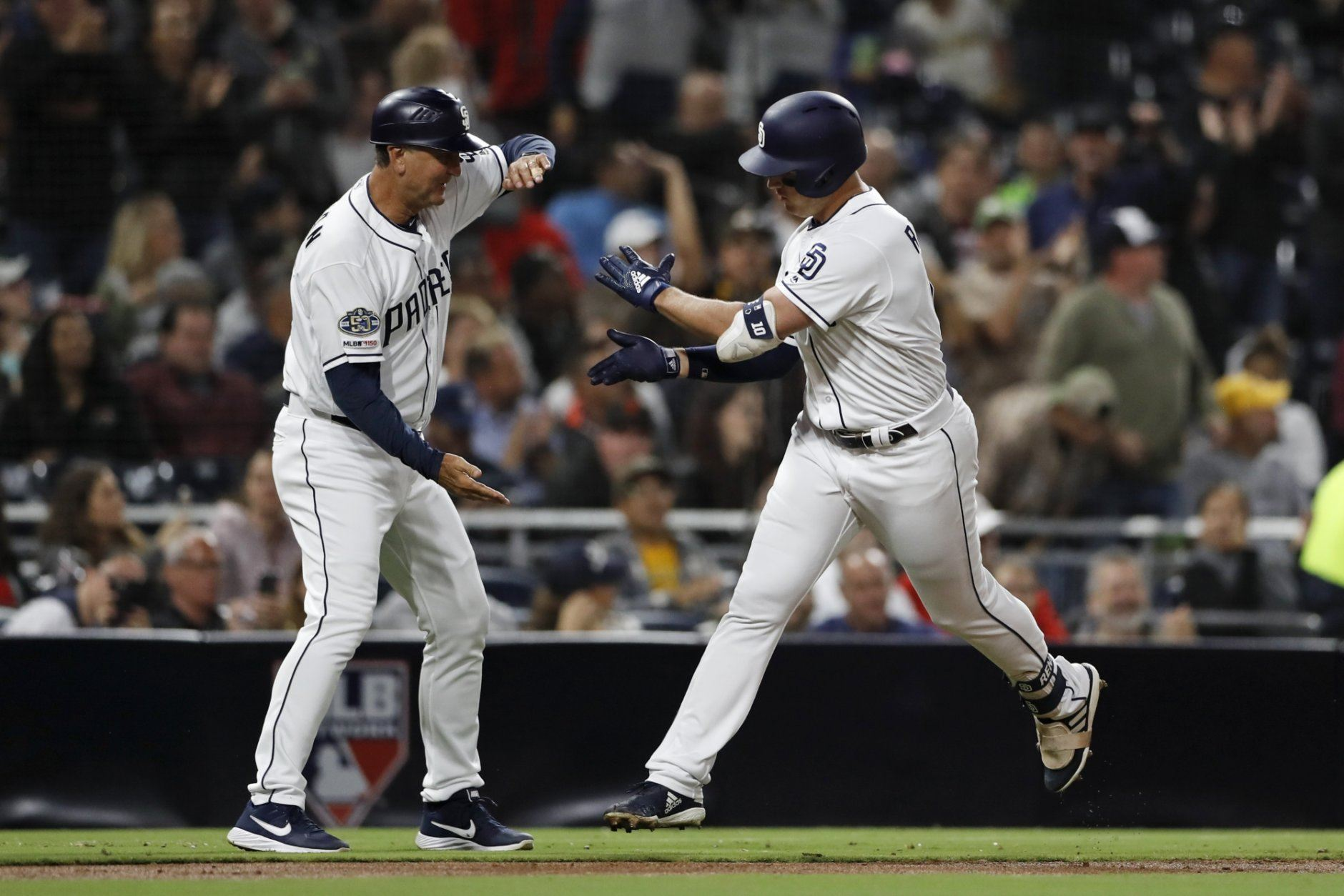 San Diego Padres' Hunter Renfroe, right, is greeted by third base coach Glenn Hoffman after hitting a two-run home run during the second inning of the team's baseball game against the Washington Nationals on Thursday, June 6, 2019, in San Diego. (AP Photo/Gregory Bull)