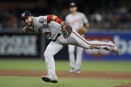 Washington Nationals second baseman Brian Dozier throws to first for the out on San Diego Padres' Manny Machado during the third inning of a baseball game Thursday, June 6, 2019, in San Diego. (AP Photo/Gregory Bull)