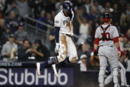 San Diego Padres' Fernando Tatis Jr., center, jumps after scoring against the Washington Nationals during the eighth inning of a baseball game Thursday, June 6, 2019, in San Diego. (AP Photo/Gregory Bull)