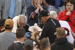 Emergency personal keep a towel on the face of a person who was struck by a line drive by Chicago White Sox's Eloy Jimenez during the fourth inning of a baseball game against the Washington Nationals, Monday, June 10, 2019, in Chicago. (AP Photo/Charles Rex Arbogast)