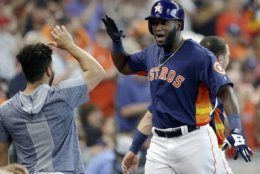 Houston Astros designated hitter Yordan Alvarez, right, gets a high-five from Jose Altuve after hitting a two-run home run during the fourth inning of a baseball game Sunday, June 9, 2019, in Houston. (AP Photo/Michael Wyke)